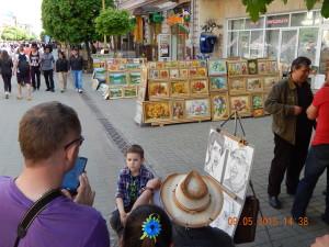 Виставка картин біля Союздруку і художник малює шарж