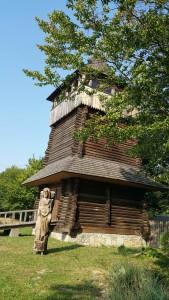 Башта у Крилосі та дерев'яні скульптури перед нею
