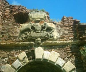 Герб і плита із написом над воротами