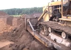 Бульдозер загортає яму після закінчення розкопок
